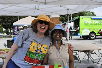 Gloria Bartas, left,children's librarian at the Govans Library, hugs branch manager Poonam Mukherjee during the Govanstowne Farmers Market on July 10.