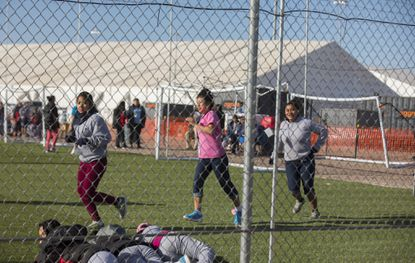 In this Nov. 25, 2018 photo, migrant teens held inside the Tornillo, Texas detention camp run while looking at protesters waving at them from outside the fences.