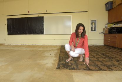 Principal Nicole Norris shows a first grade classroom at Pretty Boy Elementary School where carpets are being replaced with tiles through the Aging Schools Program.