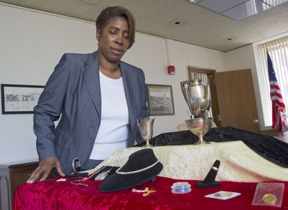Unclaimed property manager Tamarra Eaton poses with a small amount of unclaimed jewelry and other items.