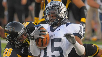 New Hampshire wide receiver R.J. Harris is tackled by Towson safety Jordan Dangerfield (20) and Thomas Bradley.
