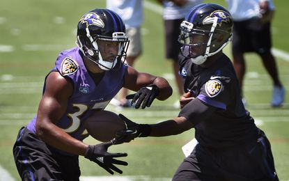 Ravens running back Buck Allen, left, receives a handoff from quarterback Josh Johnson during an OTA practice Tuesday at Under Armour Performance Center.