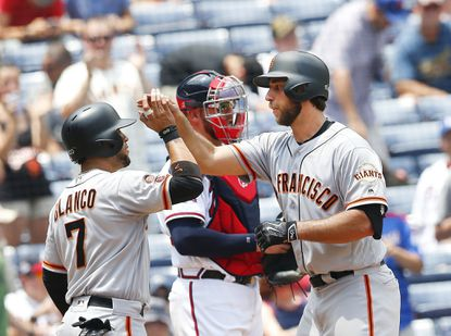 San Francisco Giants starting pitcher Madison Bumgarner, right, celebrates with Gregor Blanco (7) after hitting a two-run home run as Atlanta Braves catcher Tyler Flowers looks on in the background in the fifth inning of a baseball game Thursday, June 2, 2016, in Atlanta.