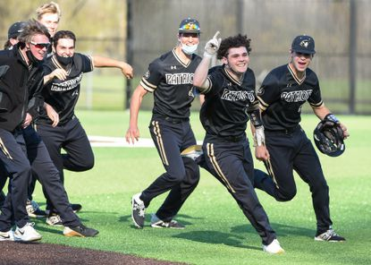 John Carroll's Mason Deletis (30), second from right, runs around the field with his team after winning the game. Archbishop Curley baseball travels to John Carroll on Tuesday, April 20, 2021.