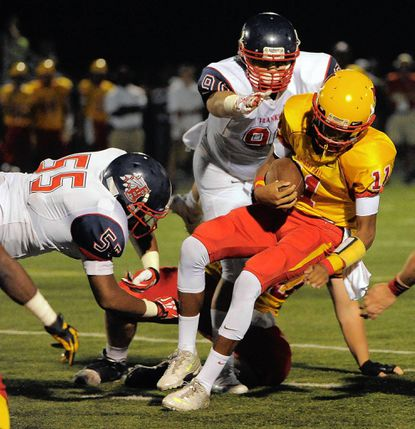 Calvert Hall cornerback Kenji Bahar is stopped by Franklin Indians defensive linemen Marcus Williams, left, and Julius Fakhoury in the Indians' 28-14 loss on Sept. 7.