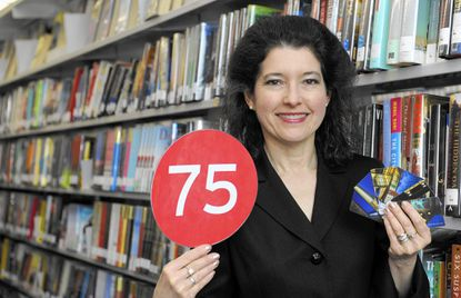 Valerie Gross, president and CEO of the Howard County Library System, holds a 75 placard and library cards which commemorate the library's 75th anniversary amid shelves of books at the system's East Columbia branch.