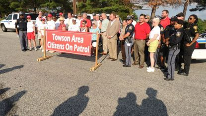 Members of the Towson Area Citizens on Patrol, local police, and others, pose at Towson's National Night Out event in 2016. Members of the citizens' group are teaming up with county police to train community members in how to deal with an active shooter situation.