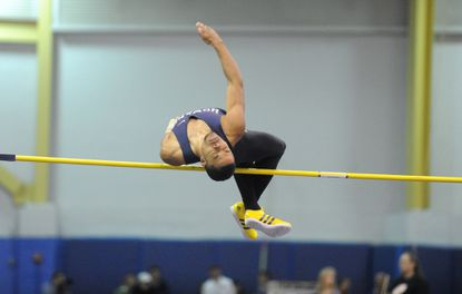 Howard's Trey Clark, clears the bar in the high jump competition during the Howard County indoor track championships.