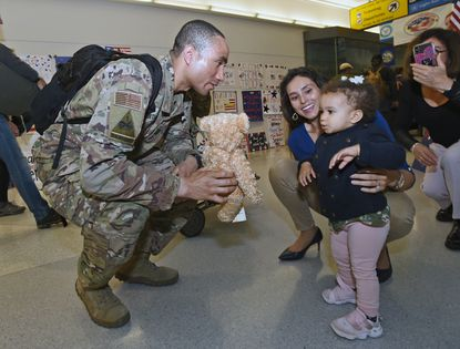 Maryland state Sen. Will Smith returns from a six-month U.S. Navy deployment to Afghanistan with new perspectives on his role as a lawmaker. In this Oct. 22, 2019, file photo, Smith, left, is greeted by his wife and daughter at BWI Thurgood Marshall Airport.