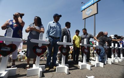 Volunteers stand with handmade crosses memorializing the victims of a mass shooting at a makeshift memorial outside Walmart, where the shooting took place, on August 5, in El Paso, Texas. The shooting left at least 22 people dead. The crosses were made by retired carpenter Greg Zanis, who has made thousands of crosses for victims of mass shootings and disasters. A 21-year-old white male shooting suspect was taken into custody in the city which sits along the U.S.-Mexico border. (Photo by Mario Tama/Getty Images)