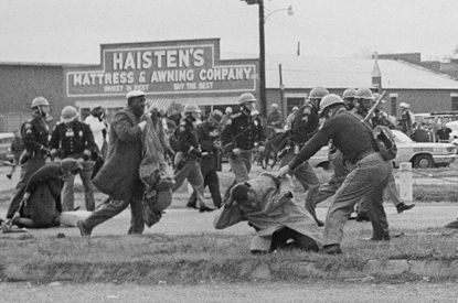 FILE - In this March 7, 1965, file photo, a state trooper swings a billy club at John Lewis, right foreground, chairman of the Student Nonviolent Coordinating Committee, to break up a civil rights voting march in Selma, Ala. The violence toward Lewis, who would go on to become a Georgia congressman, and other protesters opened Americans eyes and led to the passage of the Voting Rights Act later that year. (AP Photo/File)