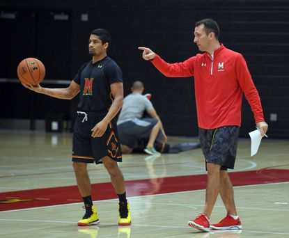 Dustin Clark (right), one of the University of Maryland basketball coaches, gives direction to scout team member Varun Ram during the scout team practice. In advance of every game, Maryland's scout team learns the other team's plays to replicate them at practice for those who will play in the game.
