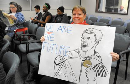 Kate Ragan holds up her sign made by Edgewood High School student and swimmer Maggie Malia before Wednesday night's School Board budget input session meeting at the School Board headquarters in Bel Air. Advocates say proposed budget cuts will decimate the Harford County Public Schools swimming program.