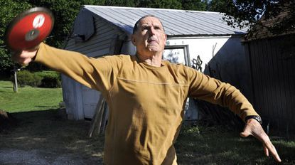 Wayne Reisberg practices the discus throw in his Marriottsville backyard. A 68-year-old volunteer track coach at Century, he competed in the Senior Olympics in Houston last month.