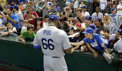 Dodgers outfielder Yasiel Puig signs autographs for fans before a game against the Diamondbacks in Arizona. For fans who don't have Time Warner Cable, leaving L.A. is one way to see their favorite club play.