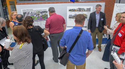 People peruse displays during a public meeting where Howard County officials present several plans they're considering to mitigate future flooding in Ellicott City. Officials field questions from a crowd gathered at Howard High School on May 2.