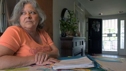 Susan Karasinski sits with a pile of legal documents and bills at her home Thursday. Her dispute with Baltimore County over a sewer bill is going to the Maryland Court of Special Appeals, the state's second highest court.