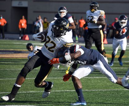 Towson wide receiver Caleb Smith, left, holds onto the ball as Morgan's Jae'Veyon Morton tries to tackle him. Sept. 4, 2021