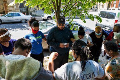 In May 2020, Matthew King, center, led a group prayer before volunteers started handing out food to families in Harlem Park, West Baltimore.