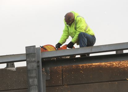 A worker repairs an Interstate 95 overpass sign and frame in 2011. The State Highway Administration is inspecting dozens of bridges after a recent incident involving a piece of concrete falling in Prince George's County.