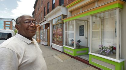 Baltimore, MD -- Cecil Clarke, owner of a set of buildings in the 1000 block of W. Baltimore Street, checks the progress of renovations. The storefronts are getting fresh facades, thanks to a city grant under a pilot program for transitional neighborhoods.