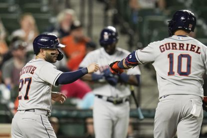 Houston Astros' Jose Altuve, left, gives a fist bump to Yuli Gurriel (10) after Gurriel drove him home on a sacrifice fly ball against the Baltimore Orioles during the seventh inning of a baseball game, Monday, June 21, 2021, in Baltimore. (AP Photo/Julio Cortez)