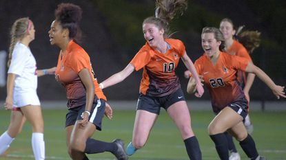 McDonogh's Lilly McCarthy (10) and Kelsey Smith (20) celebrate behind forward Aria Bilal, left, who scored the game's first goal against Archbishop Spalding in the Eagles' 5-0 victory on Saturday night.