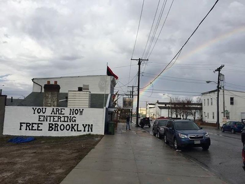"""A mural on the side of O'Flynn's Crab & Cask House in Brooklyn reads, """"You are now entering Free Brooklyn."""""""