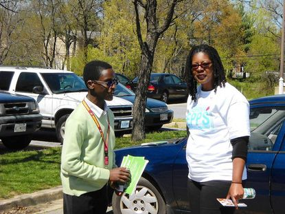 Zabrina Epps (right), a candidate for the District 1 school board seat, campaigned outside Oaklands Elementary Tuesday afternoon alongside Bowie High freshman Langston Frazier (left), who was there to support Epps' competitor, David Murray.