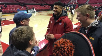 Wisconsin freshman Charlie Thomas, center, shares a laugh with his former River Hill coach Matt Graves and teammates Mike Heitzmann, left, and Ben Borucki, right, after helping the Badgers to a 70-57 victory over the University of Maryland.