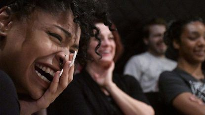 Baltimoreans Tatiana Ford (foreground) and Marie Vachino watch an improv comedy performance at Single Carrot Theatre.