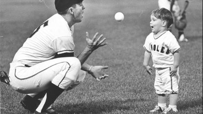 All eyes are on the ball as Brooks Robinson gets ready to catch a toss by his son Michael before an Orioles game Aug. 22, 1965, at Memorial Stadium.