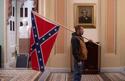 A supporter of President Donald Trump holds a Confederate flag outside the Senate Chamber during a rampage in the U.S. Capitol in Washington, D.C., on January 6.