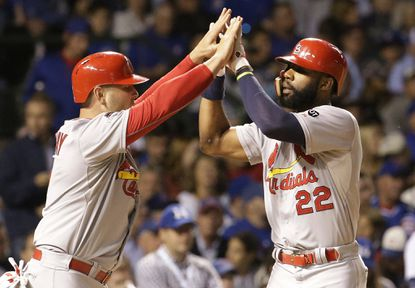 St. Louis Cardinals' Jason Heyward (22) celebrates with Matt Holliday (7) after hitting a home run against the Chicago Cubs during the sixth inning of Game 3 of the National League Division Series, Monday, Oct. 12, 2015, in Chicago.