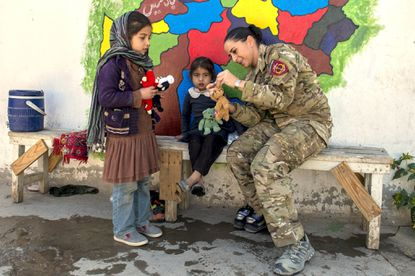 Chief Warrant Officer 3 Kaylan Harrington, an intelligence specialist who is stationed with the Maryland National Guard Special Operations Detachment in Afghanistan, delivers toys in Kabul on Nov. 6, 2017, to girls at a school her unit helped rebuild.