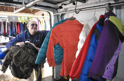 Ron Little unloads some of the coats that Admiral Cleaners in Westminster cleaned and delivered to The Shepherd's Staff for its annual Call for Coats drive.