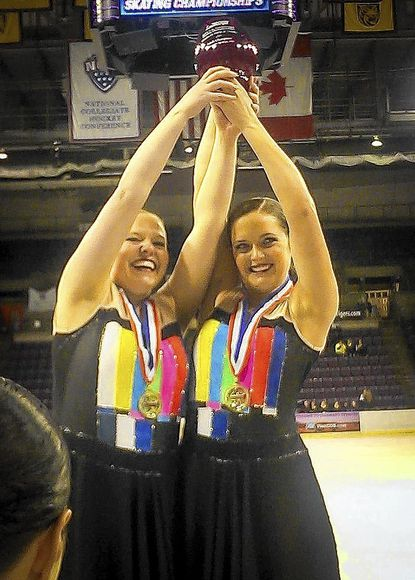 Accepting the trophy for their Gold Medal performance in synchronized skating are Kim Eddy, left, and Sarah Eddy.