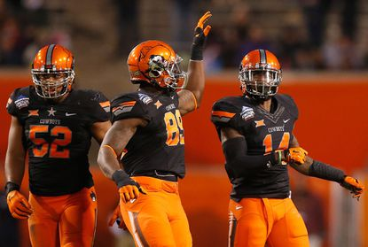 Old Mill alum Josh Furman (right) gets congratulated after a sack during Oklahoma State's 30-22 win over Washington in the Cactus Bowl.