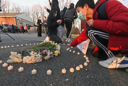 """Bill Wang, 16, right, and others place electric candles in a heart shape to commemorate the victims of the Atlanta shooting last Tuesday. At least 50 people rallied in a candlelight vigil for """"Hate Free America"""" in the wake of the killing of eight people, six of which are of Asian descent."""