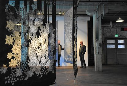 Steve Freel, left, and Jim Vose are two of the owners of Area 405, an old brewery that has been turned into an arts center and gallery space for local artists. They are pictured in the gallery area of the building. Hand cut tyvek by Zoe Friedman hangs in the space.