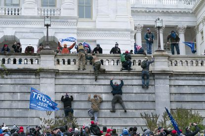 In this Jan. 6, 2021 file photo rioting supporters of President Donald Trump climb the west wall of the the U.S. Capitol in Washington. Historians say Trump's legacy and his electoral undoing will be largely shaped by rhetoric aimed at stirring his largely white base that tugged at the long-frayed strands of race relations in America. (AP Photo/Jose Luis Magana, File)