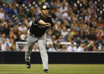 Former Colorado Rockies relief pitcher Jorge Rondon fires a throw to first after fielding a bunt by San Diego Padres' Cory Spangenberg in the eighth inning of a baseball game Friday, May 1, 2015.