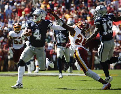 Cowboys quarterback Dak Prescott (4) breaks away from Washington cornerback Josh Norman (24) to run downfield in the first half Sunday, Sept. 15, 2019, in Landover.