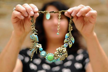 Jewelry maker Mary DeMarco shows off a peacock-themed necklace at her studio in Clipper Mill on Sept. 27. She will participate in the juried Sugarloaf Crafts Festival on Oct. 4-6 in Timonium.