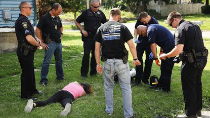 Medical workers and police treat a woman who has overdosed on heroin, the second case in a matter of minutes, on July 14, 2017, in Warren, Ohio, an area that struggles with both poverty and addiction.
