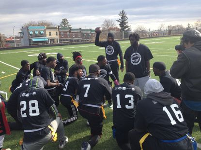 Dominic Nell (holding the football) and Genard Barr (to the right, standing) speak to community team members before the second flag football against police at Frederick Douglass High School Saturday.