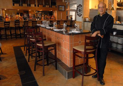 Owner Michael Tabrizi stands at the small bar seating area in the main dining room at Tabrizi's in a 2007 photograph.