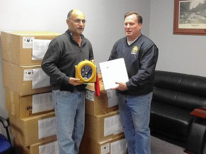 Rescue One Training for Life Inc. CEO Jeremy Gruber, left, delivers the approximately 100 AEDs donated to Laurel city to Mayor Craig Moe.