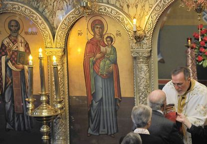 Absent their traditional gatherings and tactile rites, Orthodox Christian clergy such as the Rev. Michael Pastrikos of St. Nicholas Greek Orthodox Church in Highlandtown, prepare for their biggest holiday, Easter, at a time of social distancing. Pastrikos gives communion in this 2019 photo at St. Nicholas.