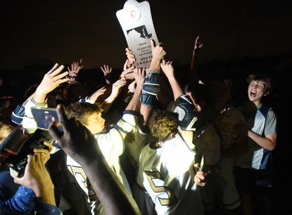 Severna Park boys lacrosse players celebrate with their Class 4A state championship trophy in the dark after beating Howard in May 2019.